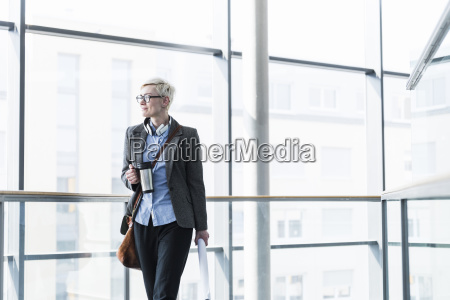 businesswoman with takeaway cup standing in