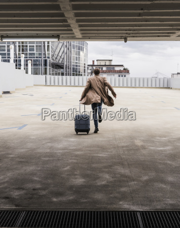 businessman with rolling suitcase in a
