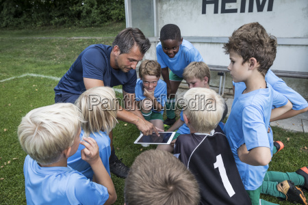 coach with tablet and young football
