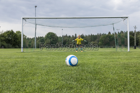 young football goalkeeper with ball on