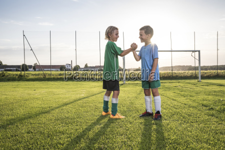 smiling young football players shaking hands