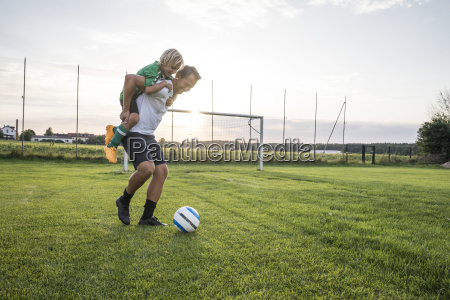 coach carrying young football player on