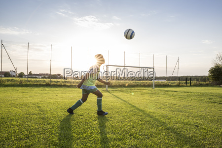 young football player heading the ball