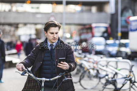 uk london businessman pushing bicycle