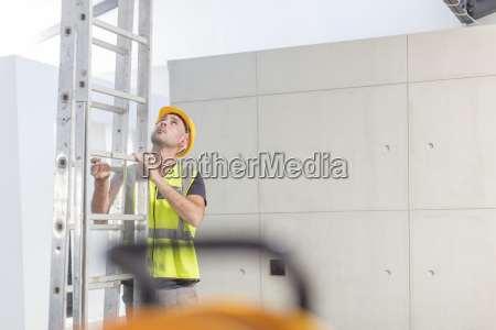 construction worker holding ladder