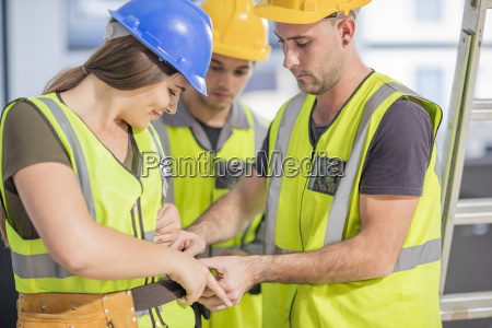 construction worker helping colleague with tool