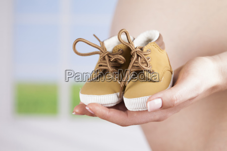 pregnant woman holding baby shoes in