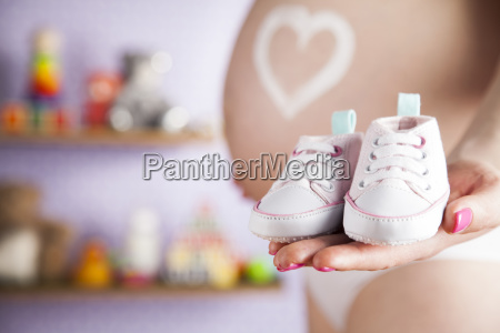 pregnant, woman, holding, a, pair, of - 25134772