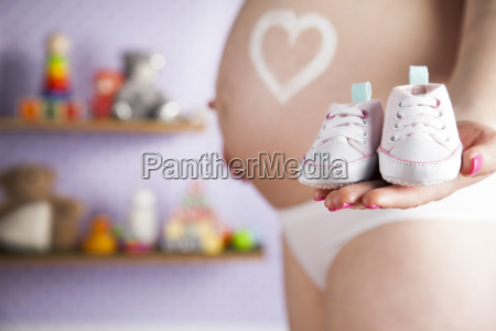 pregnant, woman, holding, a, pair, of - 25135176