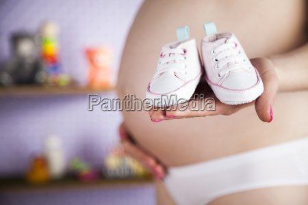 pregnant, woman, holding, a, pair, of - 25135226