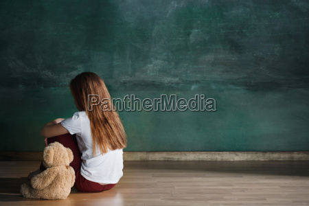 little girl with teddy bear sitting