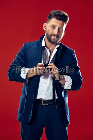 businessman tying his tie at red