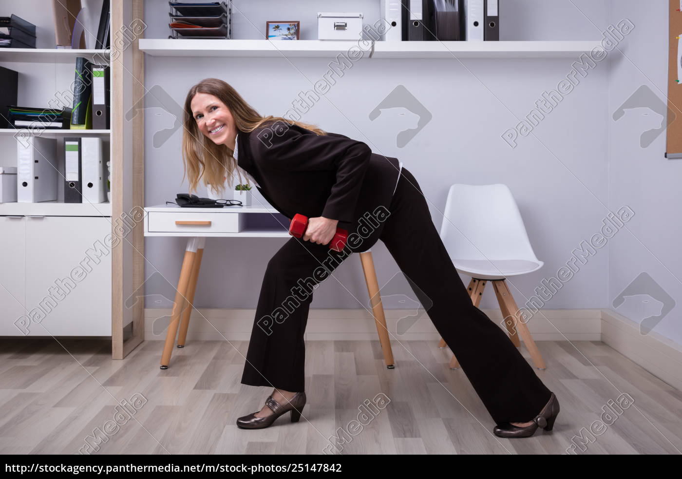 businesswoman, exercising, with, dumbbell, in, office - 25147842