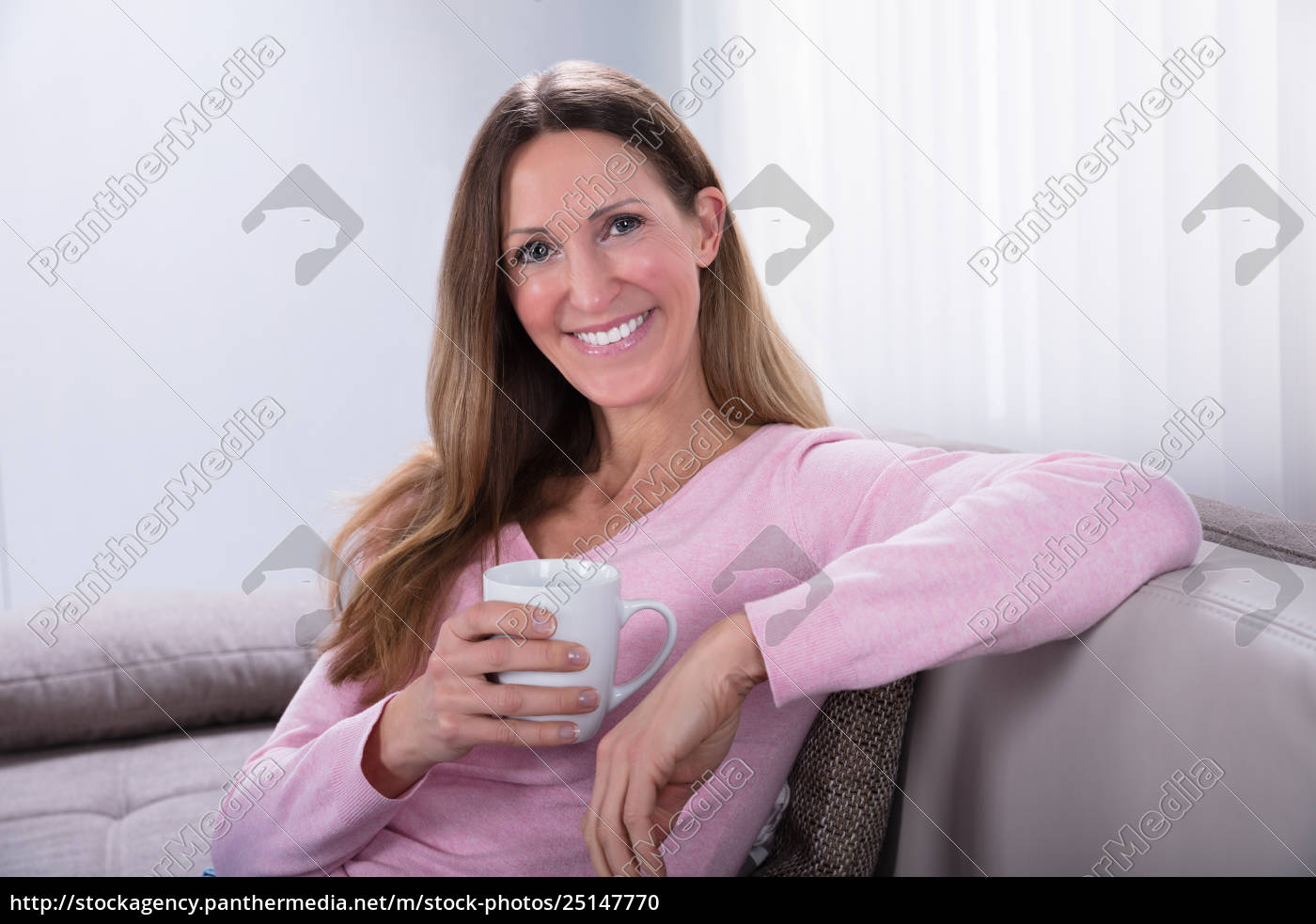 happy, woman, sitting, on, sofa, holding - 25147770