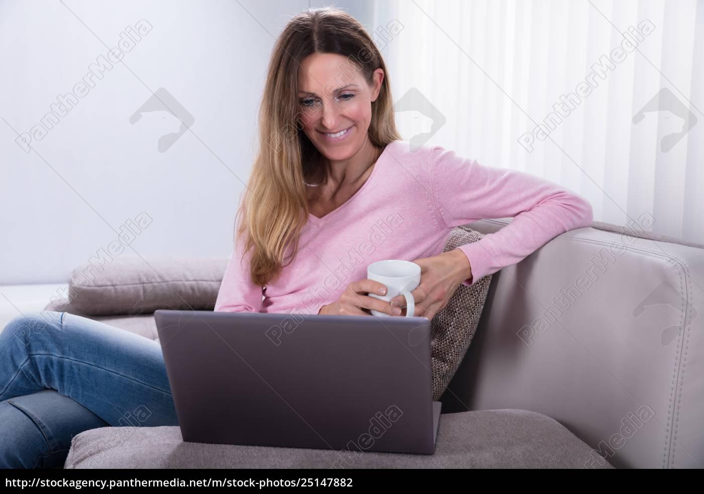 smiling, woman, looking, at, laptop - 25147882
