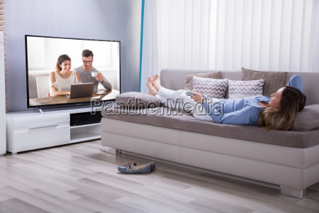 woman, lying, on, sofa, watching, television - 25147788