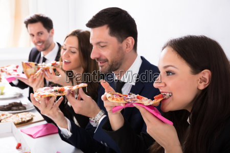 businesspeople enjoying slice of pizza