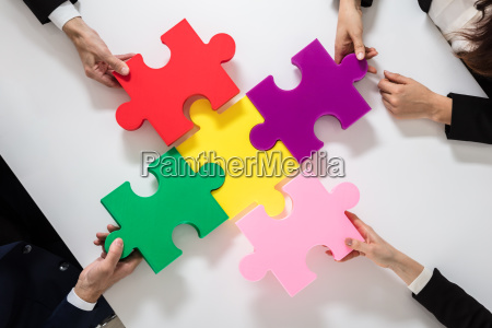 group of businesspeople solving jigsaw puzzle
