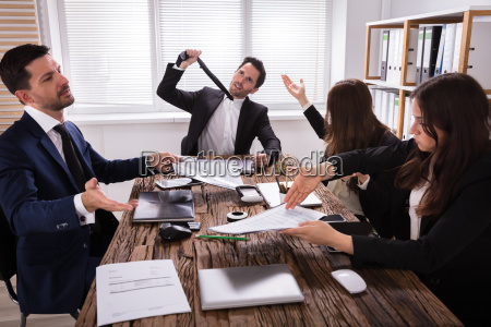 group of frustrated businesspeople in meeting