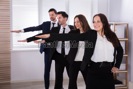 businesspeople, doing, exercise, with, hands, outstretched - 25155226