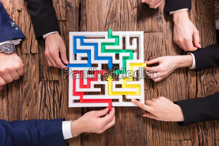 businesspeople, hand, solving, maze, together - 25155404