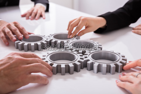 businesspeople, joining, gears, on, desk - 25155386