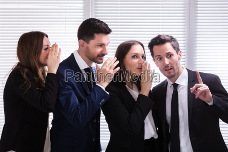 businesspeople, whispering, into, male, colleague's, ear - 25155574