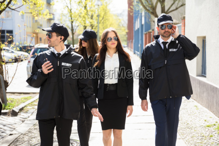 portrait, of, female, celebrity, with, bodyguards - 25155292