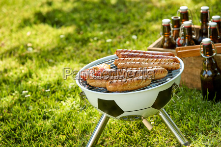 sausages grilling on a portable bbq