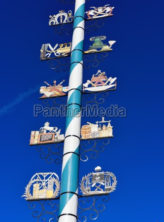 maypole with wooden signs of local