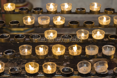 burning offering candles in a church