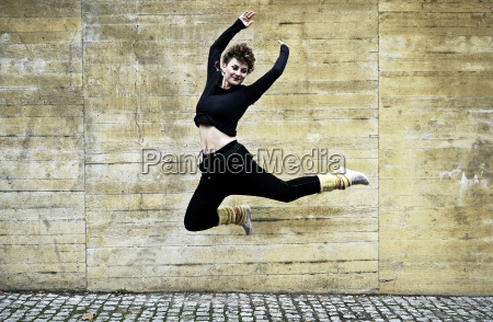 young woman jumps in front of