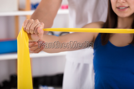 physiotherapist, assisting, woman, while, doing, exercise - 25333416