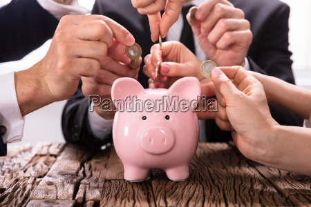 people inserting coins into piggybank