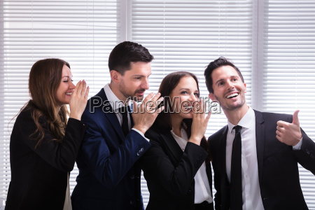 businesspeople, whispering, into, male, colleague's, ear - 25335954