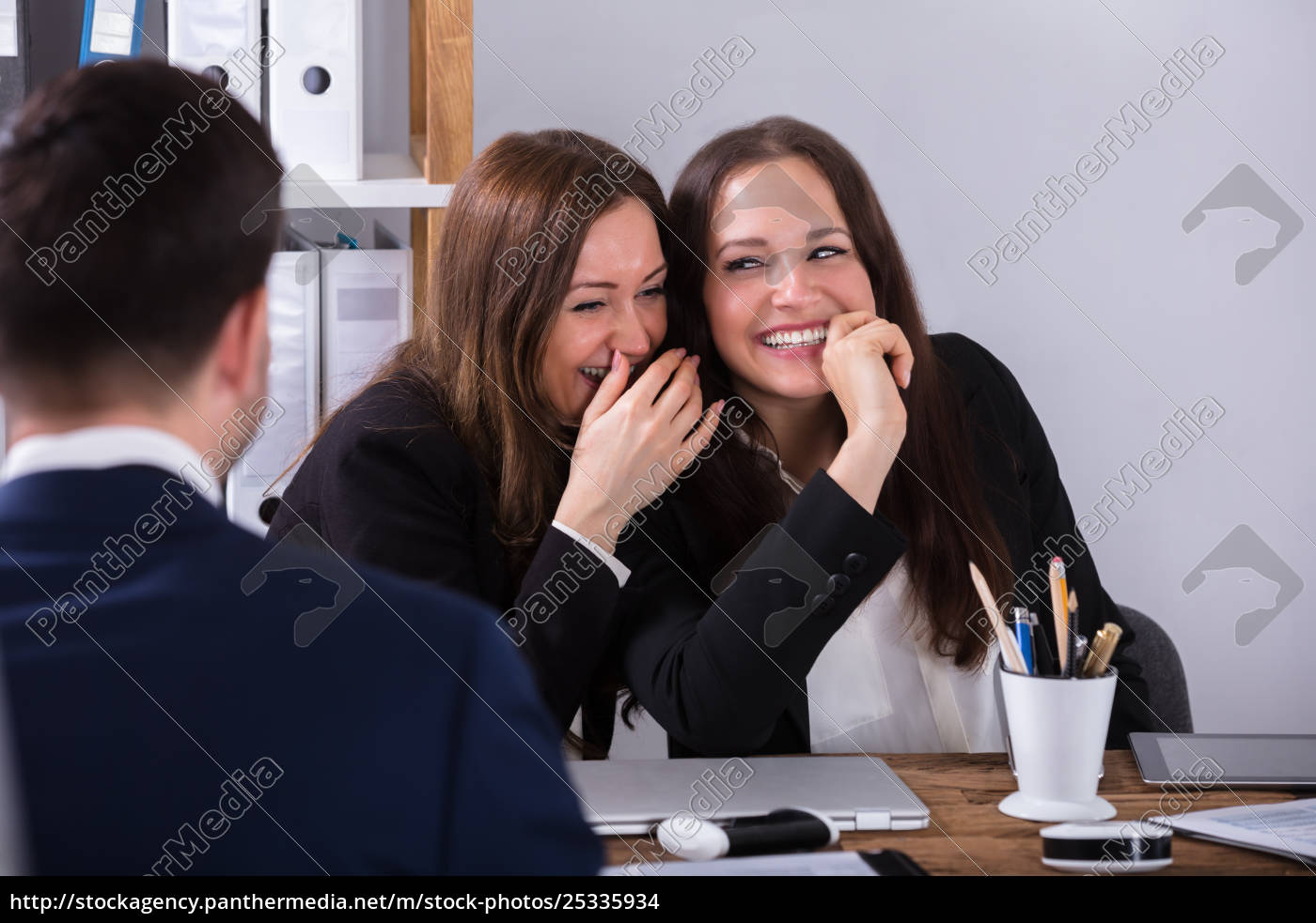 two, businesswoman, gossiping, about, male, colleague - 25335934