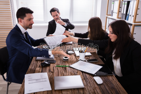 businesspeople, discussing, paperwork, in, office - 25336020