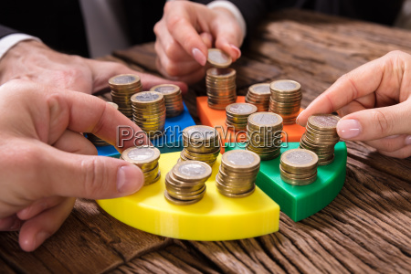 businesspeople, stacking, coins, on, pie, chart - 25336166