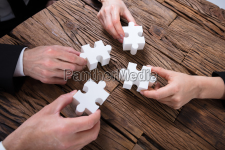 group, of, businesspeople, solving, jigsaw, puzzle - 25336156