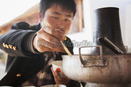chinese man eating from naxi hot