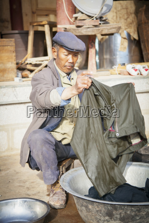 chinese naxi man cleans clothing lijiang