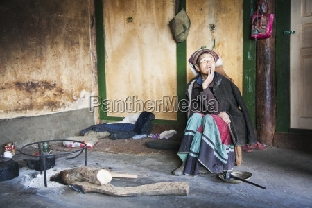naxi woman sits in very simple