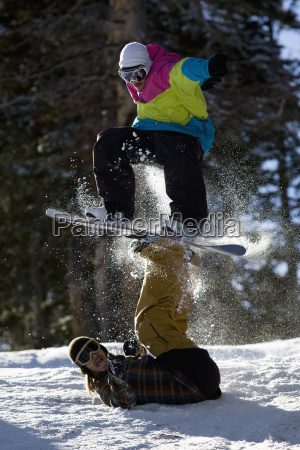 two snowboarders have fun doing a