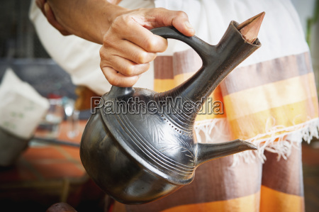 hands pouring ethiopian coffee out of