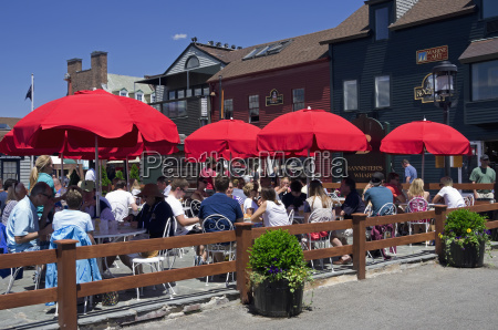 people at umbrella covered tables eating
