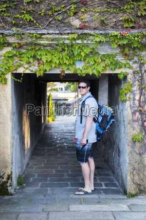 a backpacking young male tourist walks