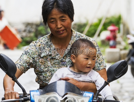 chinese woman and boy riding a