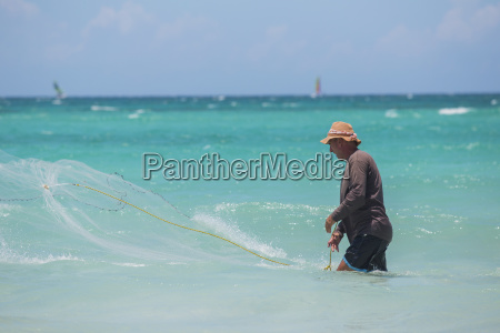 a cuban male fisherman casts a