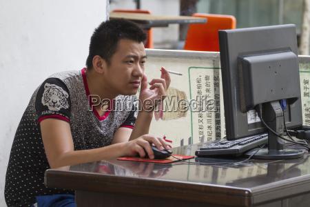 man smoking on a computer hongcun