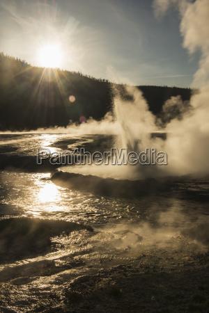 evening sun shines through a geyser